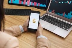 SAN FRANCISCO, USA - 18 mai 2019 : Commerçant féminin Hands Holding Smartphone utilisant l'application de l'échange de Bitrabbit  images stock
