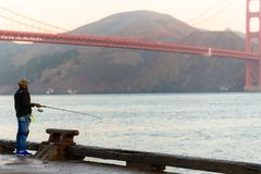 SAN FRANCISCO, USA - OCTOBER 12, 2018: A man fishing at sunrise with the Golden Gate Bridge in the background royalty free stock images