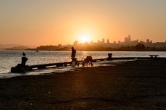 SAN FRANCISCO, USA - OCTOBER 12, 2018: Silhouette of a man fishing at sunrise with downtown background in San Francisco royalty free stock image