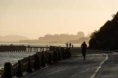 SAN FRANCISCO USA - OKTOBER 12, 2018: Folk som kör på soluppgång nära torpedhamnplats- och fortpunkt San Francisco royaltyfri foto