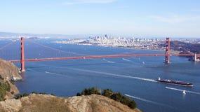 SAN FRANCISCO, USA - 4. Oktober 2014: Golden gate bridge mit SF-Stadt im Hintergrund und ein überschreitenes Schiff, von Marin He Lizenzfreie Stockfotografie