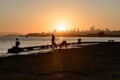 SAN FRANCISCO USA - OKTOBER 12, 2018: Kontur av en man som fiskar på soluppgång med i stadens centrum bakgrund i San Francisco royaltyfri bild