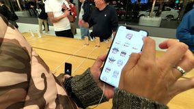 Woman testing new model Iphone XS Max at Apple store, trying to create animoji. San Francisco, USA - September 10, 2018: Woman testing new model Iphone XS Max at stock video