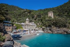 San Fruttuoso di Camogli, Ligurian coast, Genoa province, with its ancient Abbaey, the beach and tourists, Italy royalty free stock photo