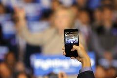SAN GABRIEL LA, CA - JANUARI 7, 2016, till och med en smart telefon, ser vi på den demokratiska presidentkandidaten Hillary Clint Royaltyfria Bilder