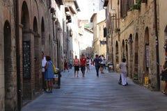 SAN GIMIGNANO ITALIEN - 14 AUGUSTI 2014, turister turnerar i den av den äldsta staden av Italien arkivfoto