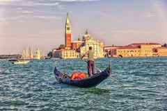 San Giorgio Maggiore and a gondolier on a gondola, view from the sea, Venice, Italy royalty free stock image