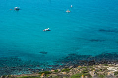 San Giovanni di Sinis coastline on a sunny day in Sardinia. Sinis peninsula, Cabras, Oristano province, Sardinia, Italy. Beautiful blue sky and some yachts in Royalty Free Stock Photo
