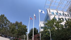 Paypal flags San Jose California. San Jose, CA, United States - August 12, 2018: USA and California flags at Paypal Headquarters in Silicon Valley. Paypal is a stock footage