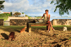 San Juan cats and woman. Beautiful woman with stray cats in San Juan, Puerto Rico, with La Fortaleza in the background Royalty Free Stock Photography