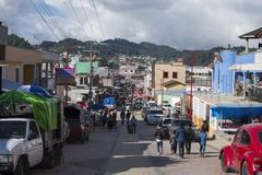 Crowded main avenue in downtown San Juan Chamula during festival. SAN JUAN CHAMULA, CHIAPAS, MEXICO - JUNE 23, 2018: Cars and people crowd the main avenue in royalty free stock photo
