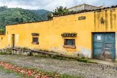 Yellow house & procession carpet in Guatemalan village royalty free stock photography