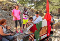 San Leo - Organ-grinder is teaching the children their craft Royalty Free Stock Photography