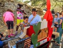 San Leo - Organ-grinder is teaching the children their craft Royalty Free Stock Photos