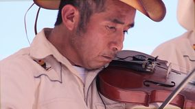 Man from the region plays a violin in the public plaza during the village festivities. SAN LUIS POTOSI, MEX 2016 (ILLUSTRATIVE IMAGE). Man from the region plays stock footage