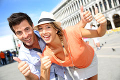 At San Marco place. Cheerful couple showing thumbs up on San Marco Place Royalty Free Stock Image