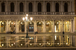 San Marco square with reflection on water at night, Venice Stock Images