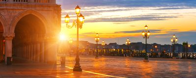 San Marco Square at sunrise, Venice, Italy. Romantic view of medieval square with rising sun and street lamps royalty free stock photography