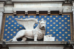 San Marco winged lion. With the book on clock tower facade, Venice, Italy Royalty Free Stock Image