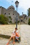 San Marino, San Marino - 10 de julio de 2017: Turistas cansados en el pie del castillo imagenes de archivo