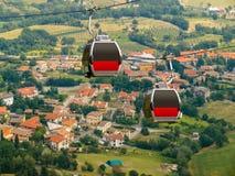San Marino - due cabine del funicolare sopra il villaggio Fotografia Stock Libera da Diritti