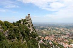 San Marino Emilia-Romagna Escúdese en la roca y la vista de la ciudad en fondo del cielo azul, visión horizontal Fotografía de archivo libre de regalías