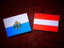 San Marino flag with Austrian flag on a tree stump  Royalty Free Stock Image