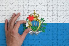 San Marino flag is depicted on a puzzle, which the man`s hand completes to fold.  stock illustration