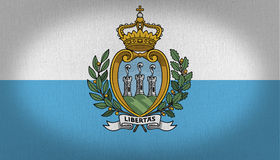 San Marino Flag. With two horizontal lines, one blue and other white whit a graphic shield in the center of it, shield with three towers over a green grass stock illustration
