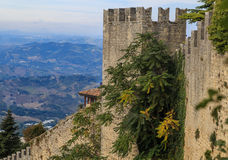 San Marino, fortified wall, summer day. Summer photo of San Marino, green hills, roofing, light clouds, fortified wall Stock Photos