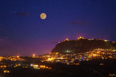 San Marino at full moon night photo with scenic sky and bright lights of night city. Stock Image