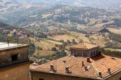 San Marino San Marino - Juli 10, 2017: Beskåda uppifrån av sikten på hus med röda tak Royaltyfri Bild