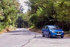 San Marino San Marino - Juli 10, 2017: Huvudväg som parkeras av den blåa bilen RENO Logan Arkivfoto