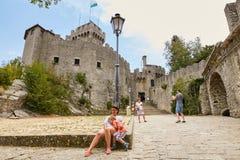 San Marino San Marino - Juli 10, 2017: Trötta turister på foten av slotten Arkivbilder
