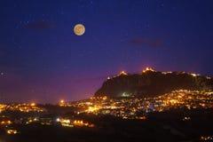 San Marino przy księżyc w pełni nocy fotografią z scenicznym niebem i jaskrawymi światłami nocy miasto Obraz Stock