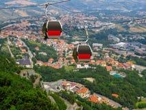 San Marino - Twee cabines van de kabelbaan over het dorp Stock Fotografie