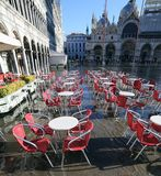 San Mark Basilica di Venezia Italia con la sedia rossa ad alta marea Fotografia Stock