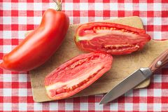 San marzano tomatoes. Halved San marzano tomatoes on cutting board. Top view Stock Photo