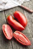 San marzano tomatoes. Halved San marzano tomatoes on old wooden table Royalty Free Stock Images