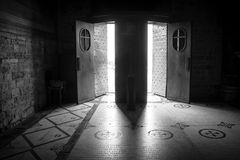 San Miniato al Monte - light through open doors. Two open doors let the light pour into the dark interior of the old medieval basilica of San Miniato al Monte in Stock Photo