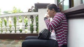 Young lady eating egg dumpling in church corridor. San Pablo City, Laguna, Philippines – December 12, 2016: Young lady eating egg dumpling in church stock video