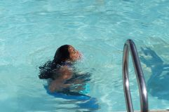Girl immerses herself in water after rigorous training for the coming annual swimming sport event. Stock Photo