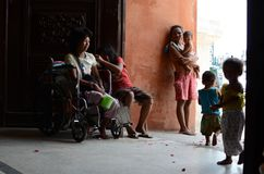 Beggar on wheelchair with other beggars and children having fun at church door gate portal. San Pablo City, Laguna, Philippines - April 29, 2017: Beggar on Stock Photography