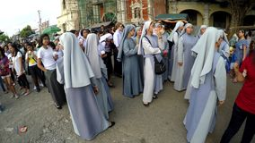 Nuns are gathered on churchyard before procession