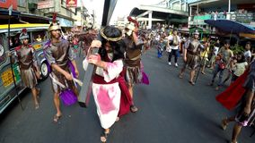 Jesus christ carrying cross whipped on street. San Pablo City, Laguna, Philippines - April 1, 2016: Unidentified people playing role of Jesus Christ carrying stock footage
