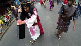 Jesus christ carrying cross whipped on street. San Pablo City, Laguna, Philippines - April 1, 2016: Unidentified people playing role of Jesus Christ carrying stock video footage