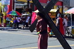 Unidentified people playing role of thieves carrying cross on street. San Pablo City, Laguna, Philippines - April 14, 2017: Unidentified people playing role of Royalty Free Stock Image