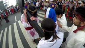 Women crying in pity approach Jesus Christ. San Pablo City, Laguna, Philippines - April 1, 2016: Unidentified women crying in pity approach role playing Jesus stock footage