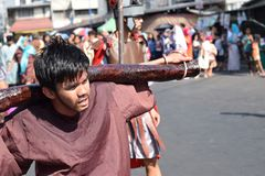 Unidentified young man playing role of thief carrying logs, street drama, community celebrates Good Friday representing the events. San Pablo City, Laguna stock photos