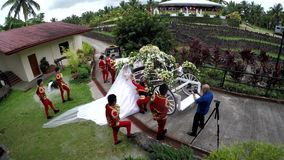 Bride escorted to wedding chariot. San Pablo City, Laguna, Philippines - August 7, 2016: Bride being escorted by uniformed attendants to her wedding chariot stock footage